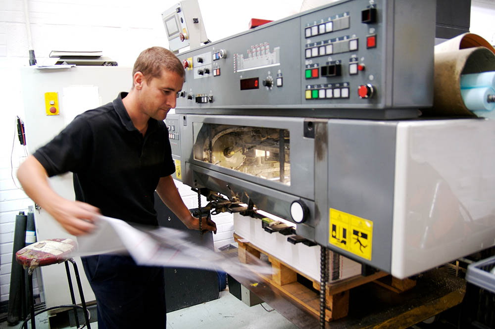 Pressman pulling sheet from printing press for inspection